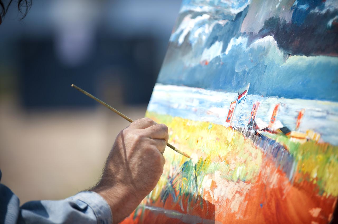 Kunstner maler bilde av en strand med flagg og stormfulle skyer